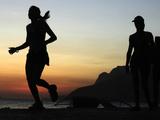 A Brazilian Woman Runs During Sunset Near Arpoador Beach in Rio De Janeiro Photographic Print by Sergio Moraes
