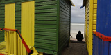 A Spectator Sits Between Beach Huts as Surfers Prepare to Take to the Water Photographic Print by Mike Hutchings