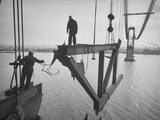 Raising the Truss, Men of the Raising Gang Ride the Swinging Steel 160 Feet Above the Water Kunst op metaal van Peter Stackpole