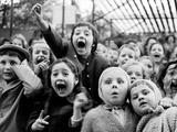 Lasten erilaisia ilmeitä nukketeatteriesityksessä sillä hetkellä, kun lohikäärme on surmattu Metallitaide tekijänä Alfred Eisenstaedt