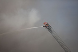 A Firefighter Battles a Fire from the Top of a Ladder Truck Photographic Print by Ben Horton