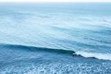 A Lone Surfer Rides a Pacific Wave Fotografisk tryk af Ben Horton