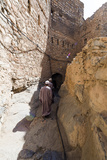 Muslim Men Walking Along a Narrow Mud Brick Alleyway in an Ancient Village in the Desert Photographic Print by Jason Edwards
