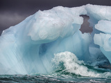 A Wave Breaks at the Base of a Blue Iceberg Photographic Print by Jay Dickman