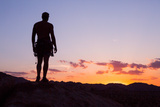 A Climber Watches the Sunset from Atop a Granite Block in Joshua Tree National Park Photographic Print by Ben Horton