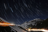 A Time-Exposure of Star Trails Above a Road with Headlights in the Snowy Alborz Mountains Photographic Print by Babak Tafreshi