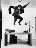 Architect and Designer Frank Gehry Jumping on a Desk in His Line of Cardboard Furniture Reproduction sur métal par Ralph Morse