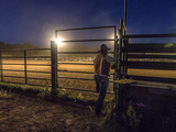 A Rodeo Performer Watches the Rodeo Action from Outside a Fence Photographic Print by Jay Dickman