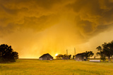 Orange Illuminated Sky as Sun Sets Behind a Supercell Thunderstorm and Shines Through a Rain Shaft Photographic Print by Mike Theiss