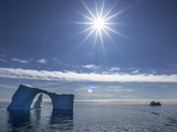 The Bright Sun over a Seascape of Icebergs, One with a Natural Arch in It Photographic Print by Jay Dickman