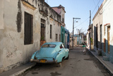 On a Street in Downtown Havana, a Classic American Car Rests on a Cinder Block as a Woman Walks By Photographic Print by Eric Kruszewski