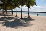 Near Beach Chairs and Palm Trees, a Couple Walks Toward the Ocean Water Photographic Print by Eric Kruszewski