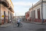 A Man Rides a Bicycle on the Street Through an Intersection in Downtown Cienfuegos Photographic Print by Eric Kruszewski