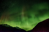 The Aurora Borealis Filling the Sky over Snowy Mountain Peaks Photographic Print by Bob Smith