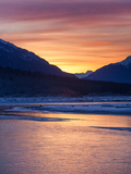 An Orange Sunrise over the Chilkat River Contrasts with the Icy Blue Mountains Photographic Print by Jak Wonderly
