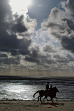 Horse Riders at Mont Saint Michel Bay. Heavy Clouds and Sunlight Above, with Virga in the Distance Photographic Print by Babak Tafreshi