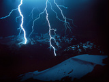 Lightning During a Storm over Snowy Mountains Photo