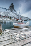 A Boat Moored in the Cold Sea in the Background the Snowy Peaks Photographic Print by Roberto Moiola
