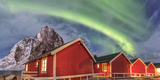 The Green Light of the Northern Lights (Aurora Borealis) Lights Up Fishermans Cabins Photographic Print by Roberto Moiola