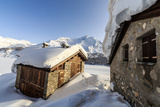The Sun, Covered with Thin Clouds, Illuminating a Typical Hut Covered with Snow at the Maloja Pass Photographic Print by Roberto Moiola