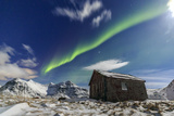 Northern Lights (Aurora Borealis) over a Small Wooden House. Flakstad Photographic Print by Roberto Moiola