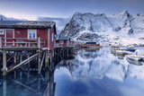 Snowy Mountains and the Typical Red Houses Reflected in the Cold Sea at Dusk Photographic Print by Roberto Moiola