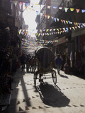 A Rickshaw Driving Through the Streets of Kathmandu, Nepal, Asia Photographic Print by John Woodworth