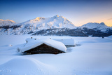 Some Scattered Huts in a Snowy Landscape at Spluga by the Maloja Pass with Magical Sunset Colors Fotografisk tryk af Roberto Moiola
