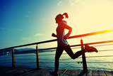 Healthy Lifestyle Sports Woman Running on Wooden Boardwalk Sunrise Seaside Photographic Print by  lzf