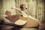 Cute Dreamer Boy Playing with a Cardboard Airplane. Childhood. Fantasy, Imagination. Retro Style. Fotografisk trykk av  prometeus
