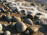 Water Washes up on Smooth Stones Lining a Beach Kunst på metal af Michael S. Lewis
