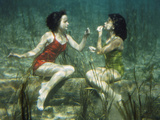 Performing swimmers put on lipstick underwater Metal Print by J. Baylor Roberts