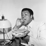 Muhammad Ali in Newcastle Eating a Stottie Cake 1977 Reproduction photographique par Dennis Hutchinson