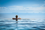 Woman Relaxing in Infinity Swimming Pool on Vacation Photographic Print by  Splendens