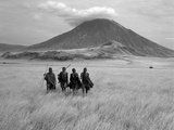 Maasai Warriors Stride across Golden Grass Plains at Foot of Ol Doinyo Lengai, 'Mountain of God' Fotografisk tryk af Nigel Pavitt