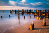 Long Exposure at Sunset of Pier Pilings in the Delaware Bay at Sunset Beach, Cape May, New Jersey. Photographic Print by Jon Bilous