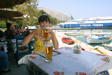 Woman Enjoying a Drink in a Harbourside Taverna, Poros, Kefalonia, Greece Photographic Print by Peter Thompson