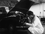 Auto Electrician Changing a Light Bulb on a Morris Minor, Nottingham, Nottinghamshire, 1961 Photographic Print by Michael Walters