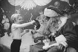 Boy Kissing African American Santa Claus in Unidentified Department Store. 1970 Photographic Print by Ralph Morse