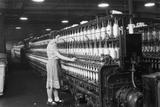 Woman Standing at Long Row of Bobbins, at a Textile Factory Photo