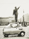 A Man Standing on Top of a Small Three-Wheeled Car Waving across the Newly Constructed Berlin Wall Photo