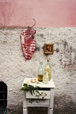 Raw Pork Ribs Hanging on the Wall of a House, Next to a A Gold-Framed Picture Photographic Print by Maria Brinkop