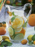 Jug of Water with Citrus Fruit, Lemon Balm and Ice Cubes Photographic Print by F. Strauss