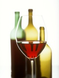 Glass of Red Wine in Front of Three Wine Bottles Photographic Print by Joerg Lehmann