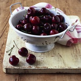 Red Cherries in a Colander on an Old Wooden Chopping Board Photographic Print by Michael Paul