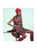 Model, Sitting on White Slat, Wears Bright Red and Blue Aztec-Print Sleeveless Coat Premium Giclee Print by Gianni Penati