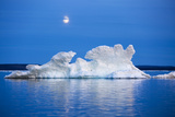 Canada, Nunavut, Moon Rises Behind Melting Iceberg in Frozen Channel Photo by Paul Souders