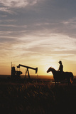 Old West, New West, Man Sitting on Horse with Oil Refinery at Sunset Photographic Print by David R. Frazier