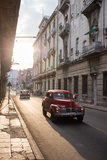 Vintage Cars Drive Down a Street in Havana Photographic Print by Erika Skogg