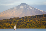 A Sailboat in Lake Villarrica Passes by the Villarrica Volcano Photographic Print by Mike Theiss